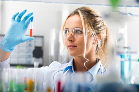 85043459-young-attractive-female-scientist-in-protective-eyeglasses-and-gloves-examining-test-tube-with-red-l